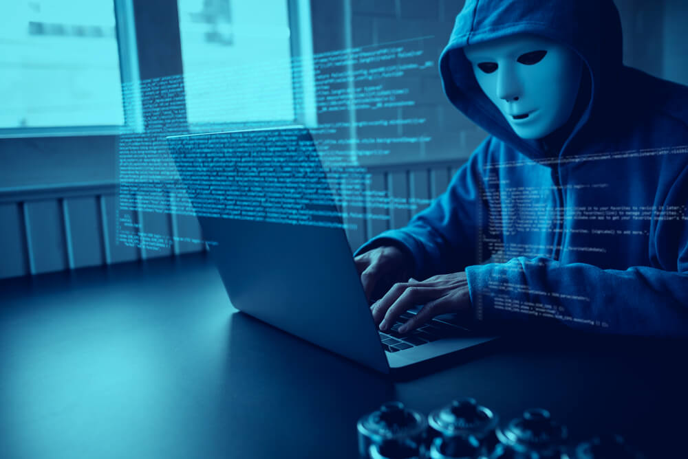 a hacker wearing a mask while doing a cyber attack