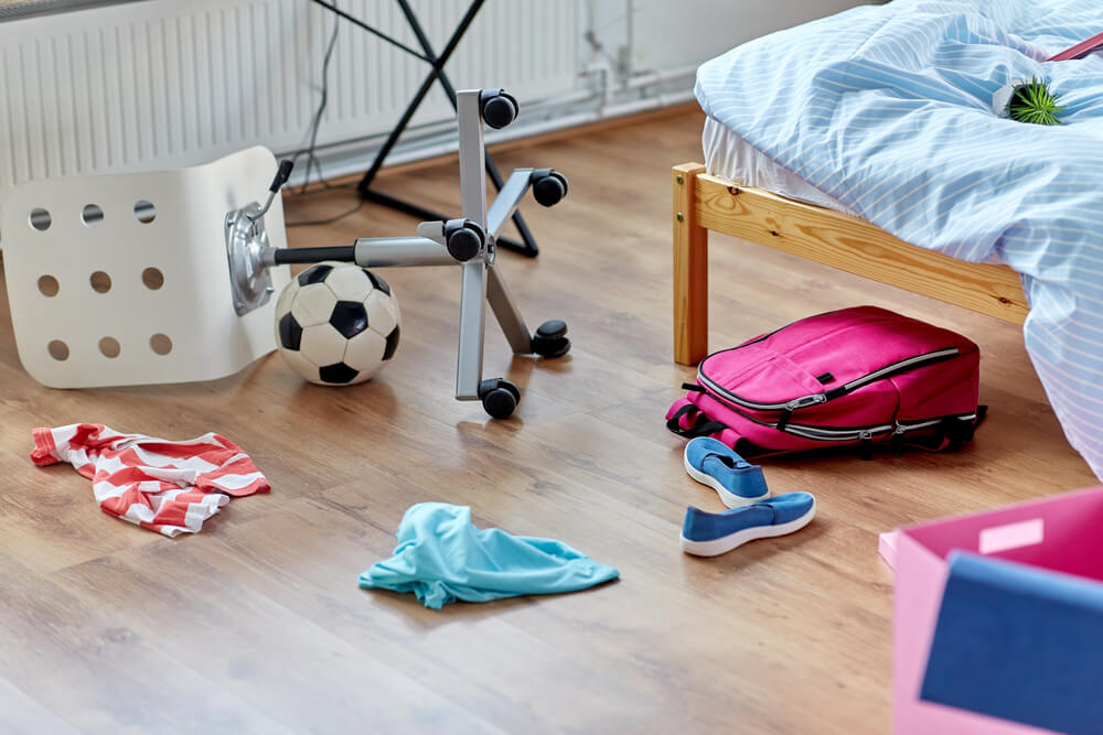 kids room with scattered toys, clothes, and bag where robot vacuum gets stuck